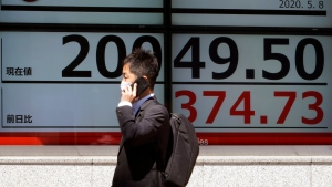 A man wearing a face mask to help curb the spread of the coronavirus walks past an electronic stock board showing Japan's Nikkei 225 index at a securities firm in Tokyo Friday, May 8, 2020. (AP Photo/Eugene Hoshiko)