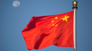 The moon sets above a Chinese flag flying over Tiananmen Square after a flag raising ceremony on National Day, the 66th anniversary of the founding of the People's Republic of China, in Beijing, Thursday, Oct. 1, 2015. (AP Photo/Mark Schiefelbein)