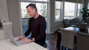 Neal Browning works on his laptop in the kitchen of his home, Monday, March 16, 2020, in Bothell, Wash., north of Seattle. (AP Photo/Ted S. Warren)