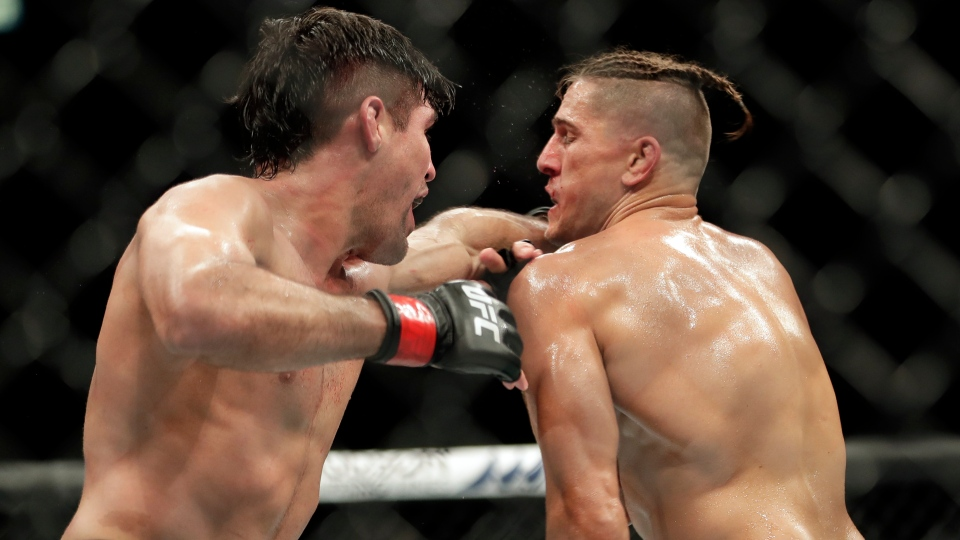 Vicente Luque, left, lands a punch against Niko Price during a UFC 249 mixed martial arts bout Saturday, May 9, 2020, in Jacksonville, Fla. (AP Photo/John Raoux)