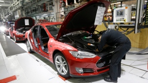 In this May 14, 2015, file photo, Tesla employees work on a Model S cars in the Tesla factory in Fremont, Calif.  (AP Photo/Jeff Chiu, File)