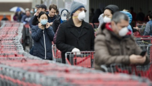 People wait in line to enter a Costco store in Toronto on Monday, April 13, 2020. THE CANADIAN PRESS/Nathan Denette