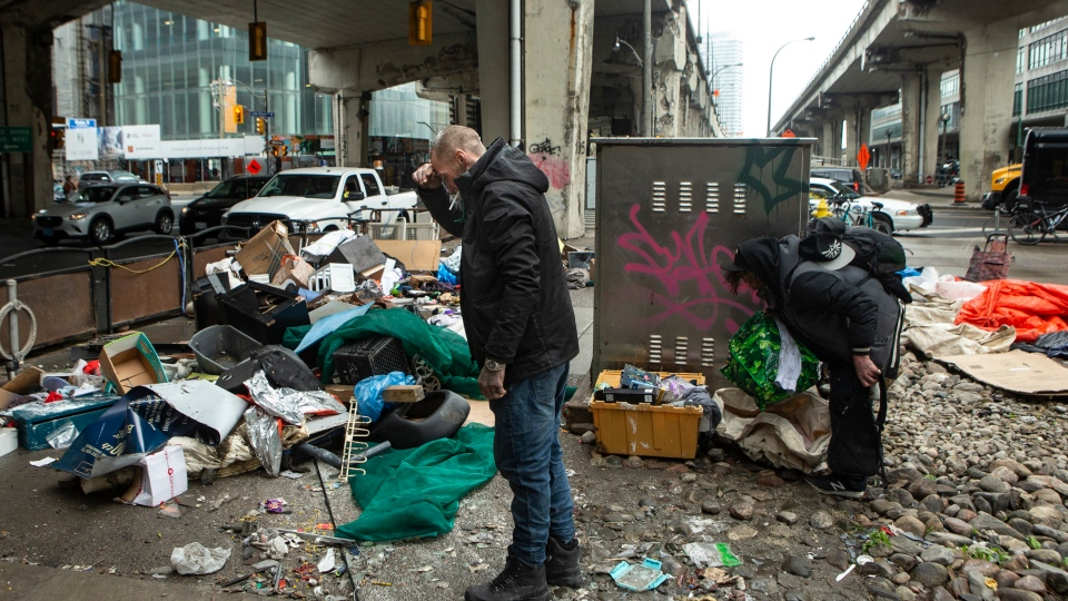 Two men who lived in an encampment on Toronto's Bay Street, collect their belongings as the city tears down the dwelling, on Friday May 15, 2020. The city is clearing homeless camps in downtown Toronto as part their COVID-19 strategy. THE CANADIAN PRESS/Chris Young