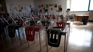 A vacant teachers desk is pictured at the front of a empty classroom is pictured. THE CANADIAN PRESS/Jonathan Hayward