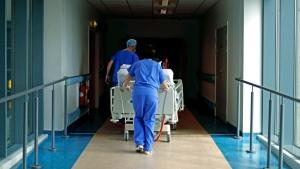 In this Thursday, May 14, 2020 photo, medical staff transfer a patient through a corridor at the Royal Blackburn Teaching Hospital, in Blackburn, England, amid the coronavirus pandemic. (Hannah McKay/Pool Photo via AP)