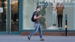 A man wearing a face mask gestures as he walks by a store on Sainte-Catherine street in Montreal, Monday, May 18, 2020, as the COVID-19 pandemic continues in Canada and around the world. THE CANADIAN PRESS/Graham Hughes