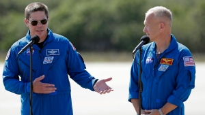 NASA astronauts Robert Behnken, left, and Doug Hurley speak during a news conference after they arrived at the Kennedy Space Center in Cape Canaveral, Fla., Wednesday, May 20, 2020. The two astronauts will fly on the SpaceX Demo-2 mission to the International Space Station scheduled for launch on May 27. (AP Photo/John Raoux)