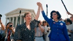 "FILE - In this April 26, 1989 file photo, Norma McCorvey, Jane Roe in the 1973 court case, left, and her attorney Gloria Allred hold hands as they leave the Supreme Court building in Washington after sitting in while the court listened to arguments in a Missouri abortion case. Three years after her death of heart failure at age 69, the woman better known as ""Jane Roe"" is making headlines again. In a documentary being released Friday, Norma McCorvey tells the audience that her support for the anti-abortion cause was an act all along. The documentary ""AKA Jane Roe"" premieres Friday on FX. (AP Photo/J. Scott Applewhite, File)"
