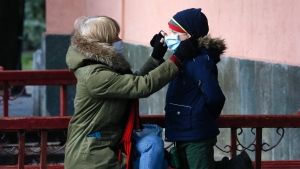 A mother puts a face mask on her child in a city park in Kyiv, Ukraine, Tuesday, March 24, 2020.(AP Photo/Efrem Lukatsky)