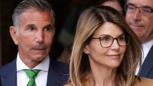 In this April 3, 2019, file photo, actress Lori Loughlin, front, and her husband, clothing designer Mossimo Giannulli, left, depart federal court in Boston after a hearing in a nationwide college admissions bribery scandal. On Thursday, May 21, 2020, the U.S. Attorney's Office in Boston said Loughlin and Giannulli have agreed to plead guilty to charges of trying to secure the fraudulent admission of their two children to the University of Southern California as purported athletic recruits. (AP Photo/Steven Senne, File)