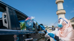 An Islamic Society of North America Mosque community member hands out candy to children in a drive through Eid celebration on Sunday, May 24, 2020. The celebration lasted hours with thousands participating. THE CANADIAN PRESS/Frank Gunn