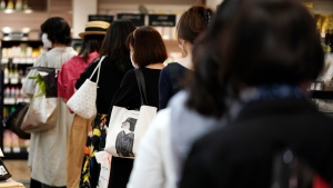 Shoppers maintain a safe social distance between each other as they wait in line to pay at a food section of the Matsuya Ginza department store which partially reopens Monday, May 25, 2020, in Tokyo. Japan's Prime Minister Shinzo Abe is expected to remove a coronavirus state of emergency from Tokyo and four other remaining prefectures later in the day. (AP Photo/Eugene Hoshiko)