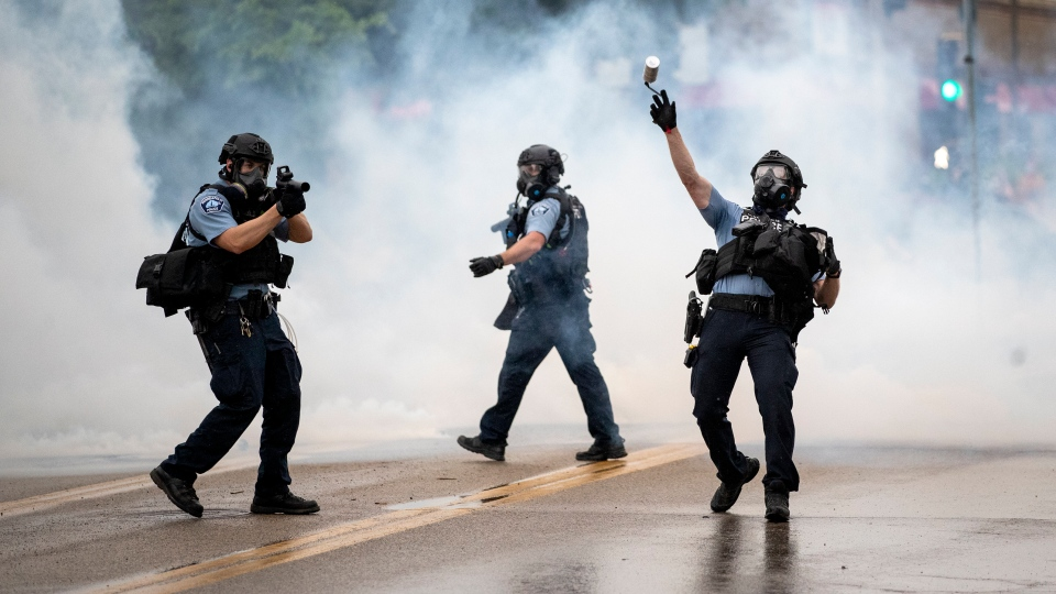 A police officer throws a tear gas canister towards protesters at the Minneapolis 3rd Police Precinct, following a rally for George Floyd on Tuesday, May 26, 2020, in Minneapolis. (Richard Tsong-Taatarii/Star Tribune via AP)