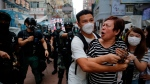 A woman argues with police as she was told to stay away from the area in Mongkok, Hong Kong, Wednesday, May 27, 2020. Thousands of protesters shouted pro-democracy slogans and insults at police in Hong Kong before lawmakers later Wednesday debate a bill criminalizing abuse of the Chinese national anthem in the semi-autonomous city. (AP Photo/Kin Cheung)