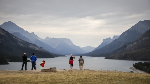 Tourists look out over Waterton Lake in Waterton National Park, Alta., Friday, Aug. 9, 2019. THE CANADIAN PRESS/Jeff McIntosh