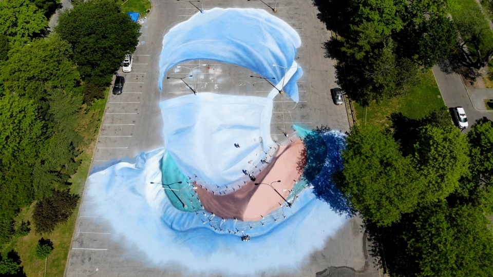 Artist Jorge Rodriguez-Gerada works on a 20,000 square foot mural of a health care worker in a parking lot in Flushing Meadows Corona Park in the Queens borough of New York, Wednesday, May 27, 2020. The mural is to honor those who lost their lives during the coronavirus pandemic, especially minority health care workers. The portrait was inspired by Dr. Ydelfonso Decoo, an immigrant doctor who died from coronavirus complications while serving hard-hit communities of color. (AP Photo/Seth Wenig)