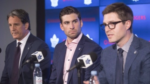 John Tavares, centre, sits alongside Toronto Maple Leafs General Manager Kyle Dubas, right, and President Brendan Shanahan following a news conference after Tavares signed with the Toronto Maple Leafs on July 1, 2018. Maple Leafs general manager Kyle Dubas, team president Brendan Shanahan and captain John Tavares spoke with the media Wednesday about the NHL's return-to-play plan. THE CANADIAN PRESS/Chris Young