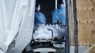 FILE - In this April 6, 2020, file photo, medical workers wearing personal protective equipment intake bodies through a tent before loading them onto a refrigerated trailer serving as a makeshift morgue at Wyckoff Heights Medical Center, in the Brooklyn borough of New York. (AP Photo/John Minchillo, File)