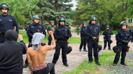 Protesters kneel before a line of police in Oakdale, Minn., Wednesday, May 27, 2020, during a demonstration outside the suburban home of former Minneapolis police Officer Derek Chauvin, one of four Minneapolis police officers fired after a black man, George Floyd, died in police custody on May 25. (AP Photo/Jeff Baenen)