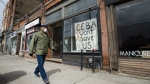 A closed store front boutique business called Francis Watson pleads for help displaying a sign in Toronto on Thursday, April 16, 2020. THE CANADIAN PRESS/Nathan Denette