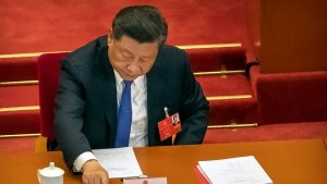 Chinese President Xi Jinping reaches to vote on a piece of national security legislation concerning Hong Kong during the closing session of China's National People's Congress (NPC) in Beijing, Thursday, May 28, 2020. China's ceremonial legislature has endorsed a national security law for Hong Kong that has strained relations with the United States and Britain. (AP Photo/Mark Schiefelbein)