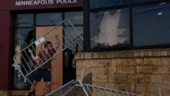 A man uses fencing to strike the Minneapolis police 3rd Precinct building during a protest Wednesday, May 27, 2020, in Minneapolis against the death of Floyd in Minneapolis police custody earlier in the week. (Christine T. Nguyen/Minnesota Public Radio via AP)