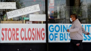 FILE - In this May 21, 2020 file photo, a man looks at signs of a closed store due to COVID-19 in Niles, Ill. The U.S. government is set to sketch its latest picture Thursday, May 28, of the layoffs that have left tens of millions of people unemployed but have slowed as states increasingly allow businesses to reopen.(AP Photo/Nam Y. Huh, File)