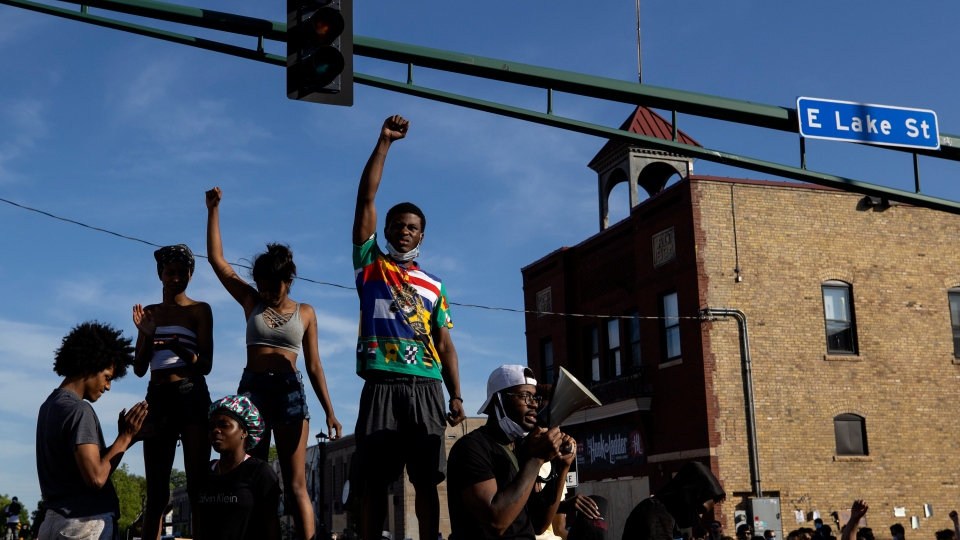 People hold a rally to protest the death of Floyd, a handcuffed black man in police custody Monday, in Minneapolis on Thursday, May 28, 2020. (Carlos Gonzalez/Star Tribune via AP)