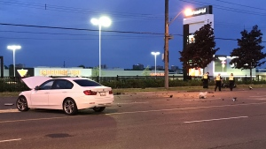 Debris is shown on roadway after a crash involving a white BMW and a motorcycle on Lawrence Avenue near Markham Road. (Michael Nguyen)