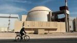 In this Oct. 26, 2010, file photo, a worker rides a bicycle in front of the reactor building of the Bushehr nuclear power plant, just outside the southern city of Bushehr. Iran said Friday, May 29, 2020, its experts would continue nuclear development activities, despite sanctions imposed earlier this week on their fellow scientists by the United States. (AP Photo/Mehr News Agency, Majid Asgaripour, File)