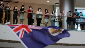"Protesters sing ""Glory to Hong Kong"" and wave a Hong Kong colonial flag in a shopping mall during a protest against China's national security legislation for the city, in Hong Kong, Friday, May 29, 2020. (AP Photo/Kin Cheung)"