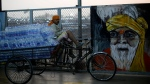 A man sits on a cart loaded with drinking water bottles to distribute to migrant workers arriving on a train from train Maharashtra state, in Prayagraj, India, Saturday, May 30, 2020. India is extending the ongoing lockdown in containment zones till June 30 but will allow all economic activities to restart in a phased manner outside these areas even though coronavirus cases continue to rise in its major cities. The upcoming reopening phase which will start Monday is called Unlock 1, the home ministry said in a directive Saturday. (AP Photo/Rajesh Kumar Singh)
