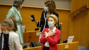 European Commission President Ursula von der Leyen, right, gestures hello to an MEP prior to addressing the European Parliament plenary in Brussels, Wednesday, May 27, 2020. The European Union is to unveil Wednesday a massive coronavirus recovery plan worth hundreds of billions of euros to help countries rebuild their ailing economies, but the bloc remains deeply divided over what conditions should be attached to the funds. (AP Photo/Olivier Matthys)