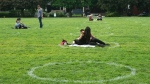 People sit within circles painted by the city in Toronto's Trinity Bellwoods Park, as a measure to enforce physical distancing, on Saturday, May 30, 2020. THE CANADIAN PRESS/Chris Young