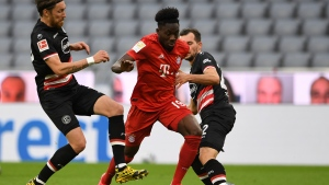 Bayern's Alphonso Davies, center, and Duesseldorf's Kevin Stoeger challenge for the ball during the German Bundesliga soccer match between FC Bayern Munich and Fortuna Duesseldorf in Munich, Germany, Saturday, May 30, 2020. Because of the coronavirus outbreak all soccer matches of the German Bundesliga take place without spectators. (Christof Stache/Pool via AP)
