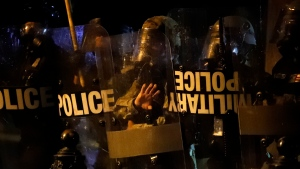 Police in riot gear watch as demonstrators gather to protest the death of George Floyd, Saturday, May 30, 2020, near the White House in Washington. Floyd died after being restrained by Minneapolis police officers. (AP Photo/Alex Brandon)