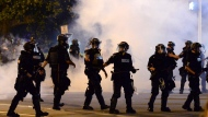 Charlotte-Mecklenburg Police Department officers begin to move forward through tear gas during a protest, Saturday, May 30, 2020, in Charlotte, N.C., as people nationwide protested the Memorial Day death of George Floyd, who died in police custody in Minneapolis. (Jeff Siner/The Charlotte Observer via AP)