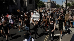 People march from Parliament Square in central London on Sunday, May 31, 2020, to protest against the recent killing of George Floyd by police officers in Minneapolis, USA, that has led to protests in many countries and across the US.(AP Photo/Matt Dunham)