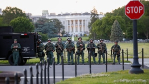 Law enforcement officers from Calvert County Maryland Sheriff's Office standing on the Ellipse, area just south of the White House in Washington, as they watch demonstrators protest the death of George Floyd, Sunday, May 31, 2020. Floyd died after being restrained by Minneapolis police officers (AP Photo/Alex Brandon)