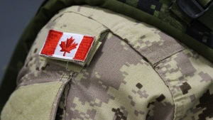 A Canadian flag patch is shown on the shoulder of a member of the Canadian forces at CFB Trenton, in Trenton, Ont., on Thursday, Oct. 16, 2014. Canadian veterans are being forced to wait on average twice as long as promised to find out whether they qualify for financial help from the government even as the backlog of unprocessed applications for assistance continues to grow. THE CANADIAN PRESS/Lars Hagberg