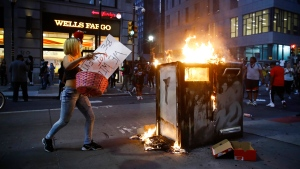 A protester throws items in to a fire Saturday, May 30, 2020, during a demonstration in Philadelphia, over the death of George Floyd, a black man who was in police custody in Minneapolis. Floyd died after being restrained by Minneapolis police on Memorial Day. (AP Photo/Matt Rourke)