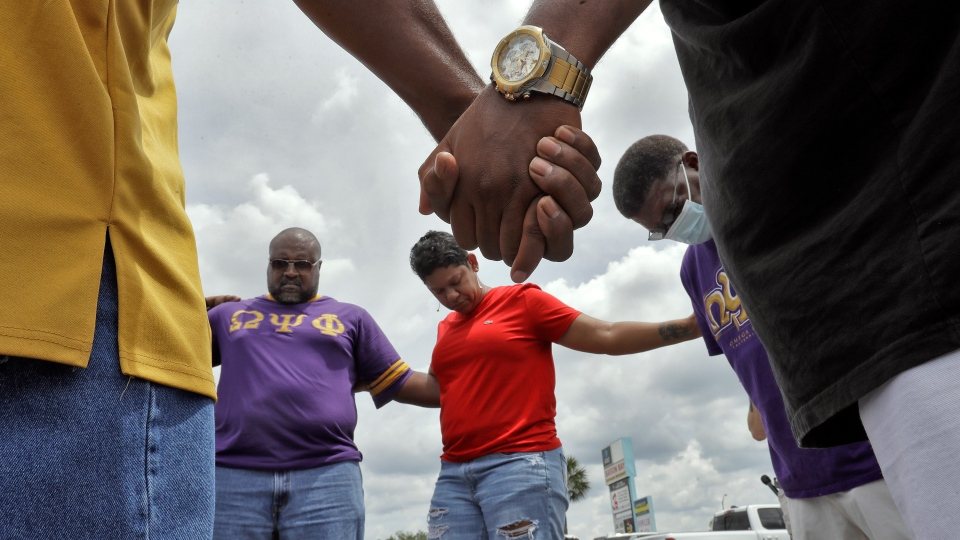 Members of the Omega Psi Phi fraternity hold hands in prayer in the parking lot, Monday, June 1, 2020, in Tampa, Fla., near where two places of business were destroyed by protesters Saturday night. Several counties across Florida issued curfews to curb large crowds gathering to protest the killings of black people by police. (AP Photo/Chris O'Meara)