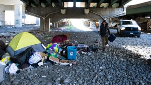 A homeless woman cleans up around her tent under the Gardiner expressway as City of Toronto workers clean up garbage during the COVID-19 pandemic in Toronto on Wednesday, May 20, 2020. THE CANADIAN PRESS/Nathan Denette