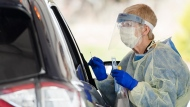 Healthcare workers do testing at a drive-thru COVID-19 assessment centre at the Etobicoke General Hospital in Toronto on April 21, 2020.  THE CANADIAN PRESS/Nathan Denette