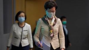 "Hong Kong Chief Executive Carrie Lam, right, arrives at a press conference in Hong Kong, Tuesday, June 2, 2020. Lam hit out at the ""double standards"" of foreign governments over national security, and pointed to recent unrest in America as an example. (AP Photo/Vincent Yu)"