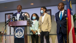 Attorney Mawuli Davis, left, speaks on behalf of Taniyah Pilgrim, center, and Messiah Young, right, during a press conference by the Fulton County District Attorney's Office in Atlanta, Monday, June 2, 2020. Six Atlanta police officers have been charged after a dramatic video showed authorities pulling the two young people from a car during protests over the death of George Floyd. At right is Fulton County District Attorney Paul Howard. (Alyssa Pointer/Atlanta Journal-Constitution via AP)