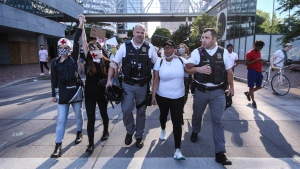 In this Monday, June 1, 2020 photo, two Portland police liaisons, escort Eboni Samuels, 41, as she speaks passionately about keeping the peace and not having protests devolve into violence in Portland, Ore. Portland will not impose a curfew on Tuesday night for the first time in four days after several thousand demonstrators remained largely peaceful during a march the night before to protest the killing of George Floyd in Minneapolis. (Beth Nakamura/The Oregonian via AP)