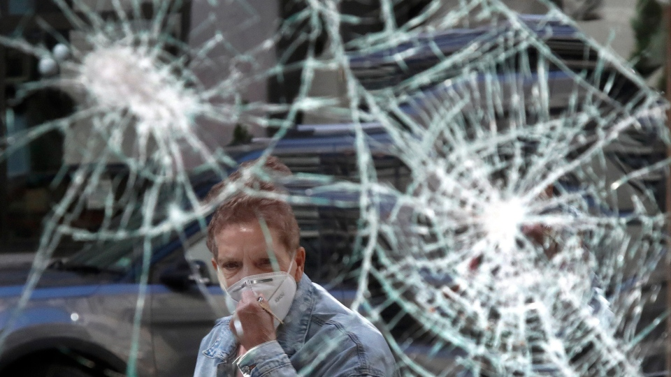 In this Monday, June 1, 2020 file photo, a woman wearing a mask due to coronavirus concerns, looks at a smashed storefront window in Boston's Downtown Crossing. The destruction caused by vandals and looters in cities across the country, who struck as demonstrators took to the streets in reaction to the killing of George Floyd in Minneapolis, has devastated small businesses already reeling from the coronavirus outbreak. (AP Photo/Elise Amendola, File)