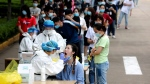 In this May 15, 2020 file photo, people line up for medical workers to take swabs for the coronavirus test at a large factory in Wuhan in central China's Hubei province. The Chinese city of Wuhan has tested nearly 10-million people for the new coronavirus in an unprecedented 19-day campaign to check an entire city. (Chinatopix Via AP)