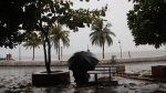 A man sit on a bench as it rains by the shores of the Arabian Sea in Mumbai, India, Wednesday, June 3, 2020. A storm in the Arabian Sea off India's west coast intensified into a severe cyclone on Wednesday, gathering speed as it barreled toward India's financial capital of Mumbai. Nisarga was forecast to drop heavy rains and winds gusting up to 120 kilometers (75 miles) per hour when it makes landfall Wednesday afternoon as a category 4 cyclone near the coastal city of Alibagh, about 98 kilometers (60 miles) south of Mumbai, India's Meteorological Department said. (AP Photo/Rafiq Maqbool)